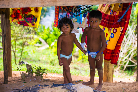 EMBERA VILLAGE, PANAMA, JANUARY 9, 2012: Unidentified native Indian brother and sister play in a cabin in Panama, Jan 9, 2012. Indian reservation is the way to conserve native culture