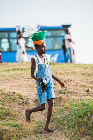 ACCRA, GHANA - MARCH 2, 2012: Unidentified Ghanaian girl carries a pelvis on her head in Ghana. People of Ghana suffer of poverty due to the unstable economic situation
