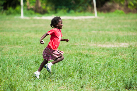 GHANA - MARCH 3, 2012: Unindentified Ghanaian girl in red clothes runs happily in the field in Ghana, on March 3rd, 2012. Children in Ghana suffer from poverty due to the unstable economical situation Editorial