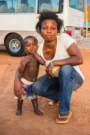 ACCRA, GHANA - MARCH 5, 2012: Unidentified Ghanaian boy with his mother in the street in Ghana. Children of Ghana suffer of poverty due to the unstable economic situation