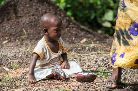 ACCRA, GHANA - MARCH 3, 2012: Unidentified Ghanaian girl sits on the ground in Ghana. People of Ghana suffer of poverty due to the unstable economic situation