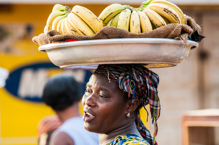 ACCRA, GHANA - MARCH 4, 2012: Unidentified Ghanaian woman carries bananas in the street in Ghana. People of Ghana suffer of poverty due to the unstable economic situation
