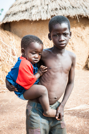 ACCRA, GHANA - MARCH 6, 2012: Unidentified Ghanaian boy holds his little brother on his hands in the street in Ghana. Children of Ghana suffer of poverty due to the unstable economic situation