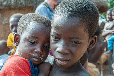 ACCRA, GHANA - MARCH 6, 2012: Unidentified Ghanaian boy and his little brother in the street in Ghana. Children of Ghana suffer of poverty due to the unstable economic situation