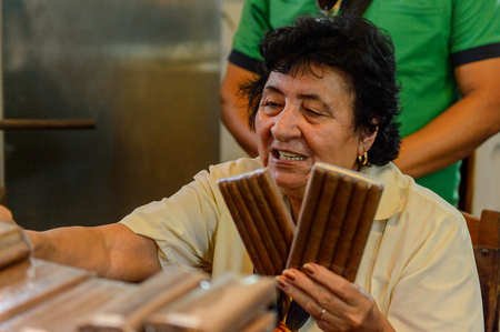 TRINIDAD, CUBA - SEP 7, 2017: Unidentified woman shows Cuban cigars to buy, part of the culture of Cuba