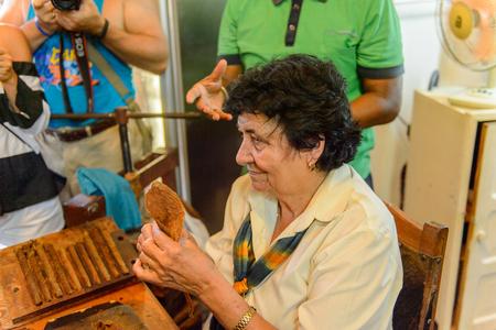 TRINIDAD, CUBA - SEP 7, 2017: Unidentified woman rolls Cuban cigars, part of the culture of Cuba