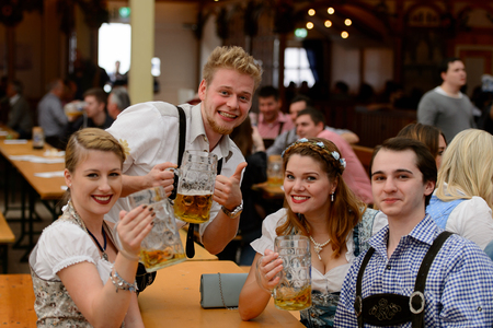 MUNICH, GERMANY - OCT 2, 2017: Unidentified friends drink beer at the Octoberfest, the world's largest festival