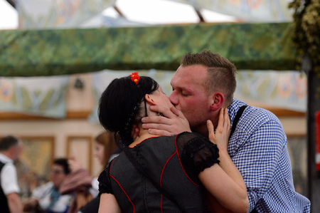 MUNICH, GERMANY - OCT 2, 2017: Unidentified girl in traditional Bavarian costume gives a kiss to a guy at the Octoberfest,  the worlds largest festival