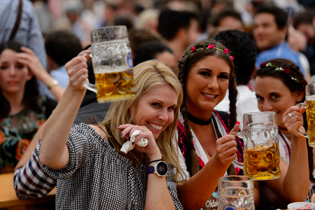 MUNICH, GERMANY - OCT 2, 2017: Unidentified beautiful girls drink beer at the Octoberfest, the world's largest festival