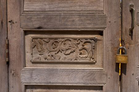 A fragment of a wooden door, decorated with hand woodcarving photo