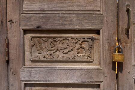 tallado en madera: Un fragmento de una puerta de madera, decorado con madera tallada a mano