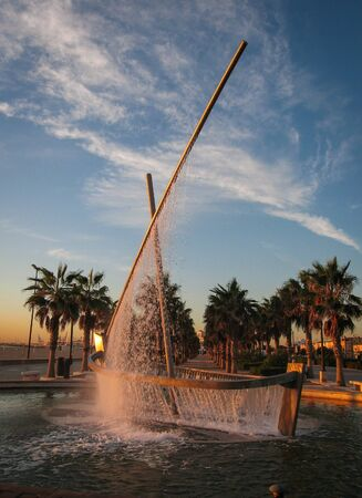valencia orange: Image of a fountain - sailboat at sunrise, Valencia, Spain