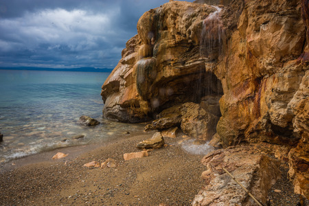 Scenic thermal waterfalls and rock formations on the beach in Loutro Edipsou, Evia, Greece photo