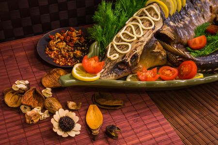 sturgeon: Image of a sturgeon decorated with lemon and tomatoes on a green plate Stock Photo