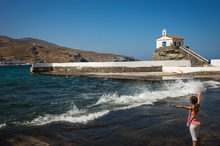 conducts: Image of little girl conducts waves and white church on the beach, Andros, Greece