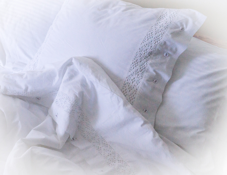 pillow case: Image of White embroidered linens, pillows and blankets Stock Photo