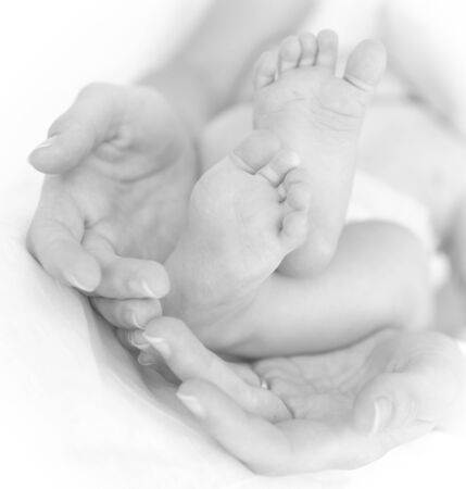 fondle: Image of mothers hands and babys legs