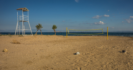scala: Volleyball tower, net and three trees on sandy beach near the town of Scala, Agistri, Greece Stock Photo