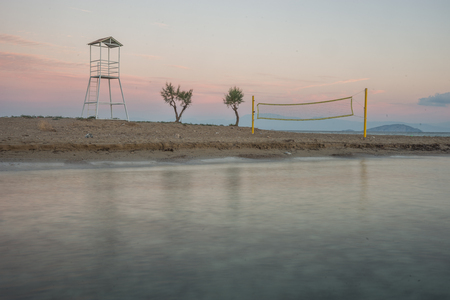 western europe: Volleyball tower, net and three trees on sandy beach near the town of Scala, Agistri, Greece Stock Photo