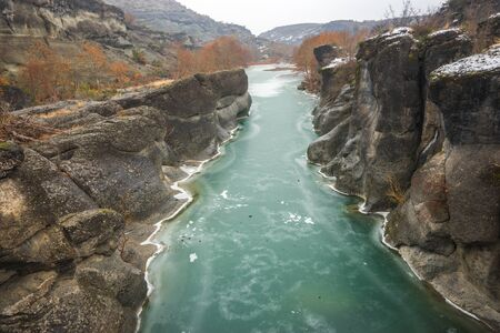water  scenic: Image of river with green waters, snow and ice near Meteora in Greece Stock Photo