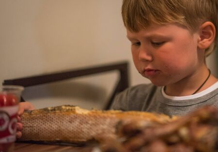 long loaf: Little boy eating long loaf bread in kitchen, Russia Stock Photo