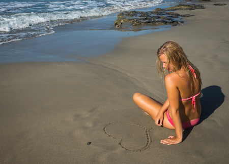 greece shoreline: Young girl in red bikini and image of heart  on  sand on beach of Crete in Greece Stock Photo