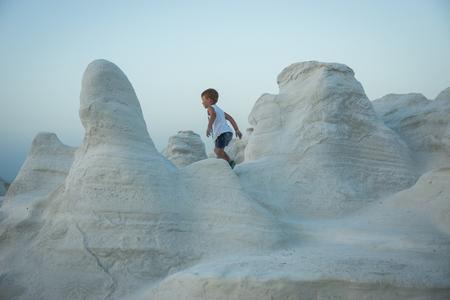 Image of little boy walking on Moonscape beach Sarakiniko, Milos, Greece Stock Photo