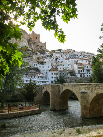 castilla: Cityscape with bridge over river at Alcala del Jucar in Castilla la Mancha, Spain Stock Photo