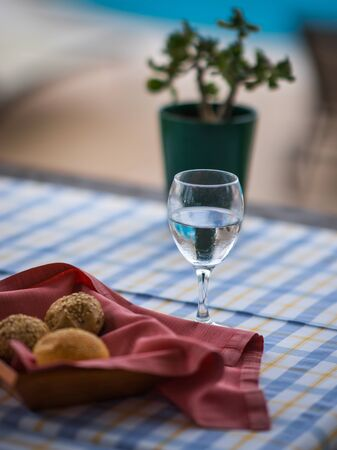 Image of buns in  basket and  glass of water on the table Stock Photo