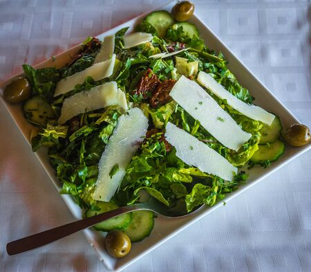 kitchen island: Image of arugula salad with parmesan cheese, dried tomatoes and olives Stock Photo