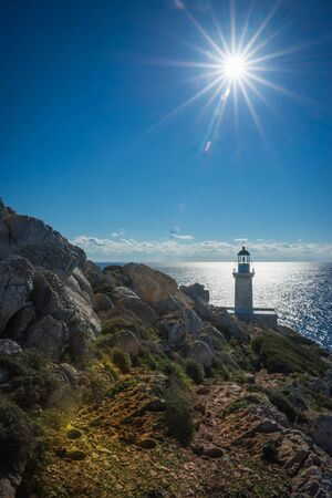 over the edge: Full sun lighting over the modern lighthouse at the most southern edge of greek mainland