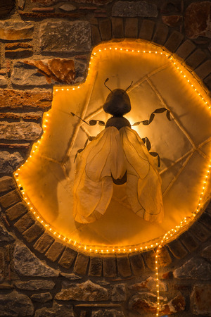 festively: Image of huge decorative fly in  festively illuminated niche in wall Stock Photo