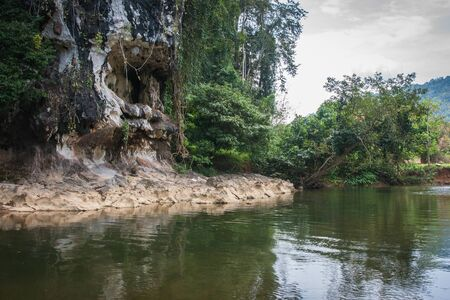 Landscape with river and grotto in the tropical rain forest of Khao Sok sanctuary, Thailand