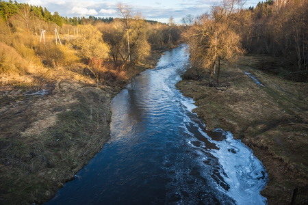 Landscape with sunset illuminated full-water river and forest in springtime near Moscow, Russia