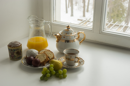 Scenic view of still life with  Easter cakes, eggs, teapot ,  cup of tea juice, grapes and pear  on a sill and trees covered with snow seen through the open window