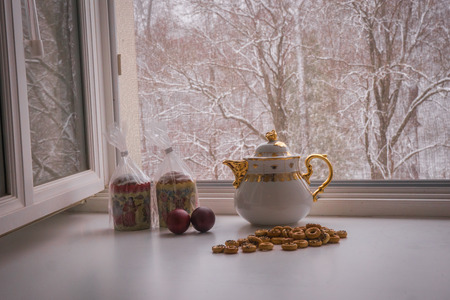 Scenic view of still life with two Easter cakes, eggs, bagels and a teapot on a sill and trees covered with snow seen through the open window