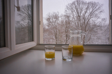 Scenic view of two glasses and a jug partially filled with orange juice on a sill and bare trees seen through the open window