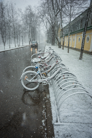 Scenic view of a row of bicycles smoothly covered with fresh snow after weather phenomena - snowfall in late April near Moscow Stok Fotoğraf