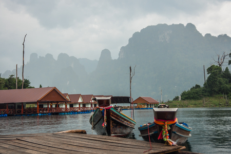 Scenic and unique landscape with floating houses and long tail boats at Chieou Laan lake, Thailand