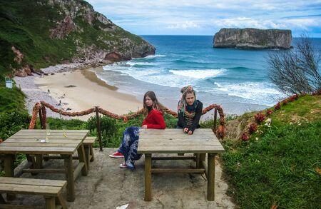 Andrin beach, Asturia y Cantabria, Spain - July 07, 2009, Two girls sitting at the table at Andrin beach, Spain