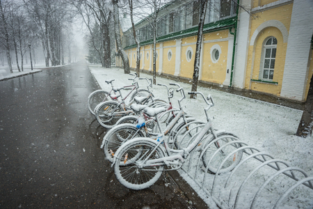 Scenic view of a row of bicycles smoothly covered with fresh snow after weather phenomena - snowfall in late April near Moscow Stock fotó