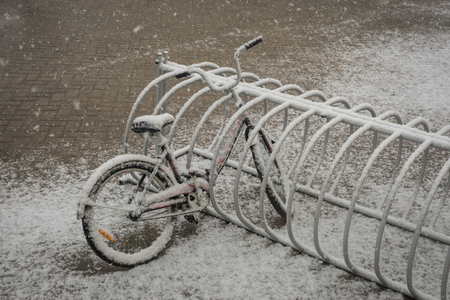 Scenic view of a lonely bicycle covered with fresh snow due to weather phenomena - snowfall in late April near Moscow