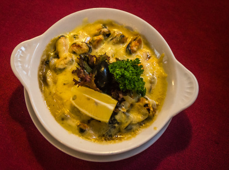 Image of mussels cooked in a lemon-mustard  and cheese sauce with mushrooms, selective focus