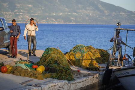 Fiskardo, Greece - April 30, 2016, Fishermen on  pier of  town of Fiscardo on island of Kefalonia in Greece Editorial
