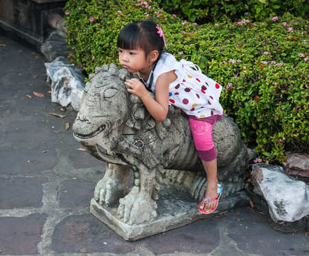 Bangkok, Thailand - January 01, 2011 :  Little Thai girl playing with stone lion in courtyard of temple in Bangkok, Thailand