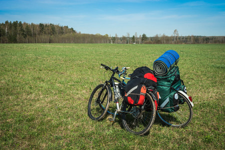 Two bicycles with luggage on meadow in Kaluga region in Russia