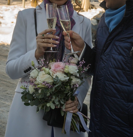 Image of hands of bride and groom with glasses of champagne and bouquet of bride