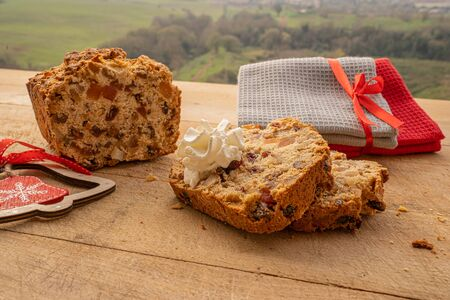 Image of christmas stollen with candied fruit, raisins, walnuts on a wooden tabletop