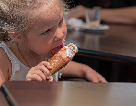 Image of little blonde girl eating white and pink ice cream in a waffle cone Reklamní fotografie