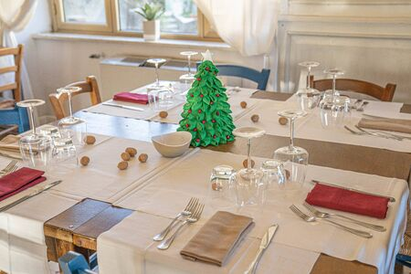 Image of dinner table with a small Christmas tree and sprinkled walnuts, selective focus
